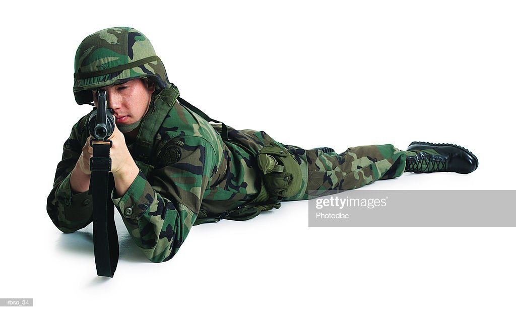 a caucasian male soldier lies on the ground and aims his rifle : Stockfoto