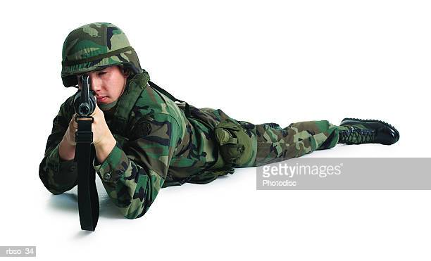 a caucasian male soldier lies on the ground and aims his rifle - boots rifle helmet stock pictures, royalty-free photos & images