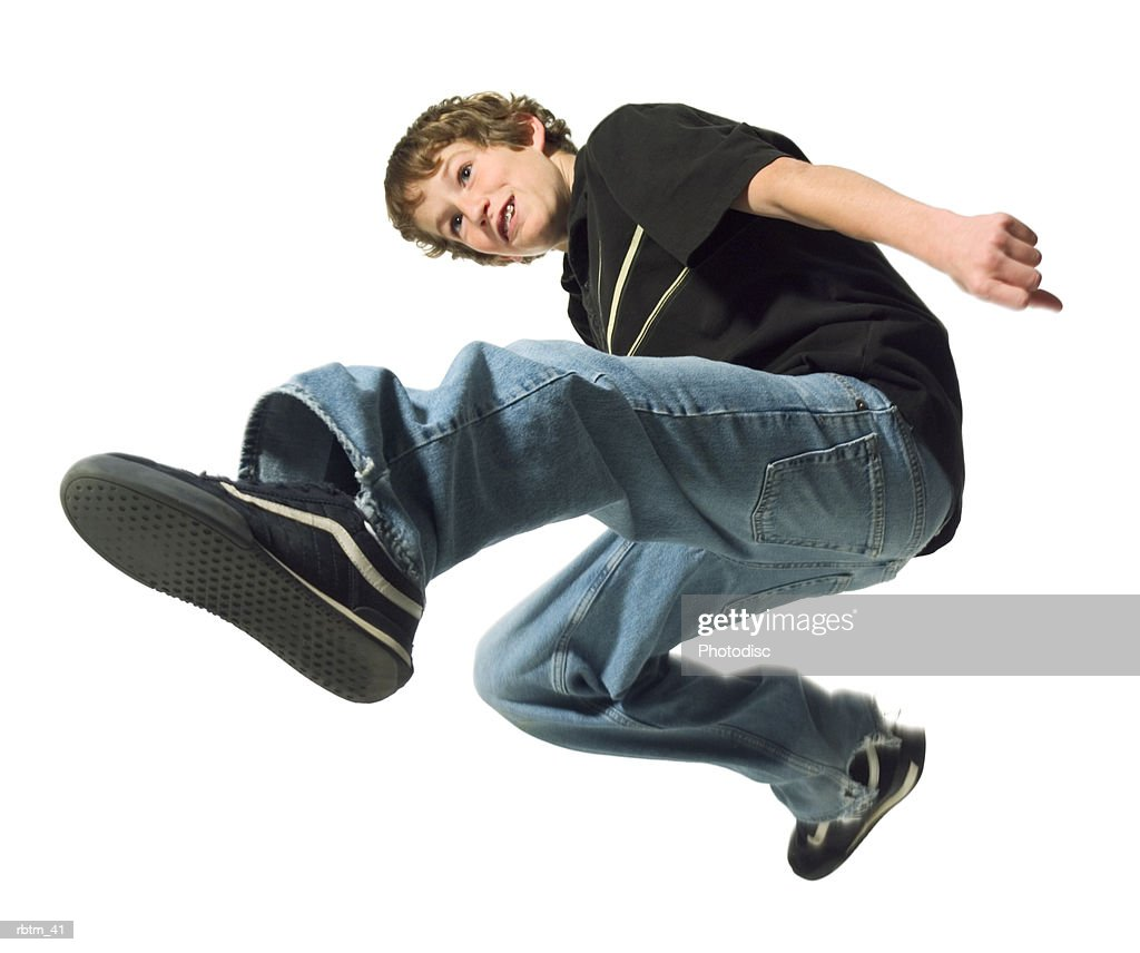 a caucasian male teen in jeans and a black shirt jumps through the air : Foto de stock