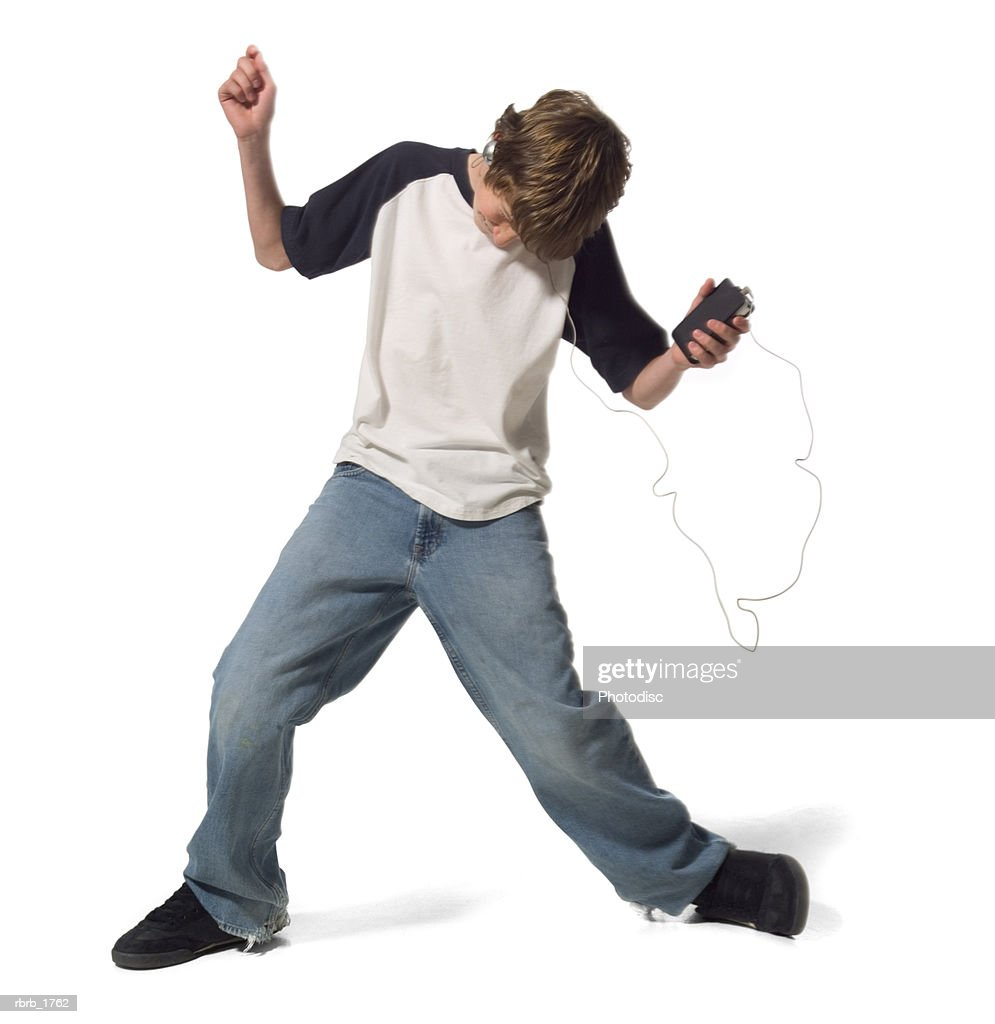 a caucasian male teen in jeans and a blue and white shirt dances as he listens to his headphones : Stockfoto