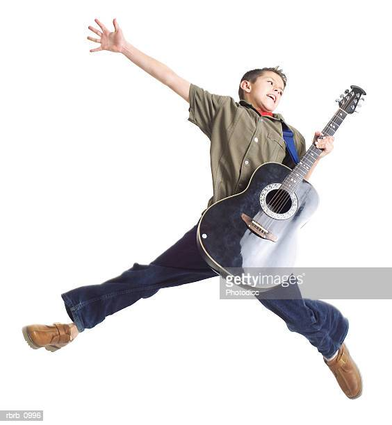 a caucasian male teen in jeans and a brown shirt jumps up into the air holding a guitar
