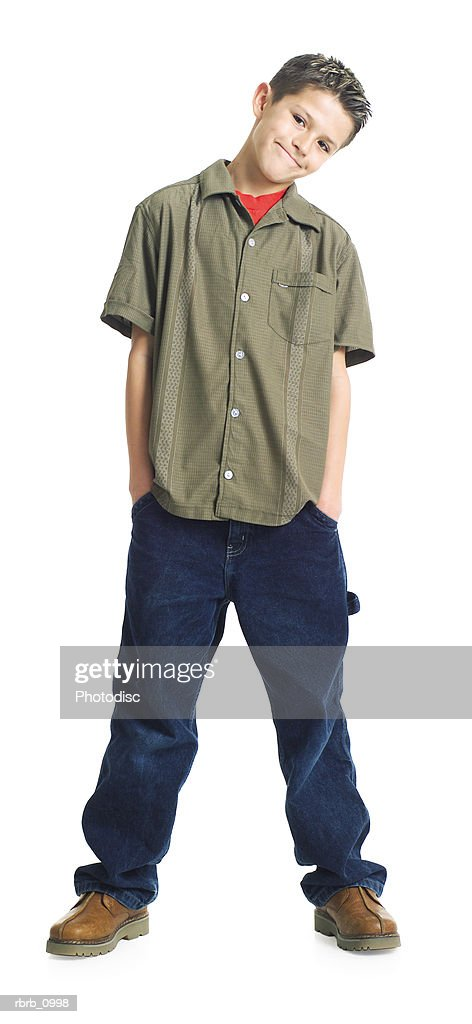 a caucasian male teen in jeans and a brown shirt puts his hands in his pockets and smiles : Stockfoto