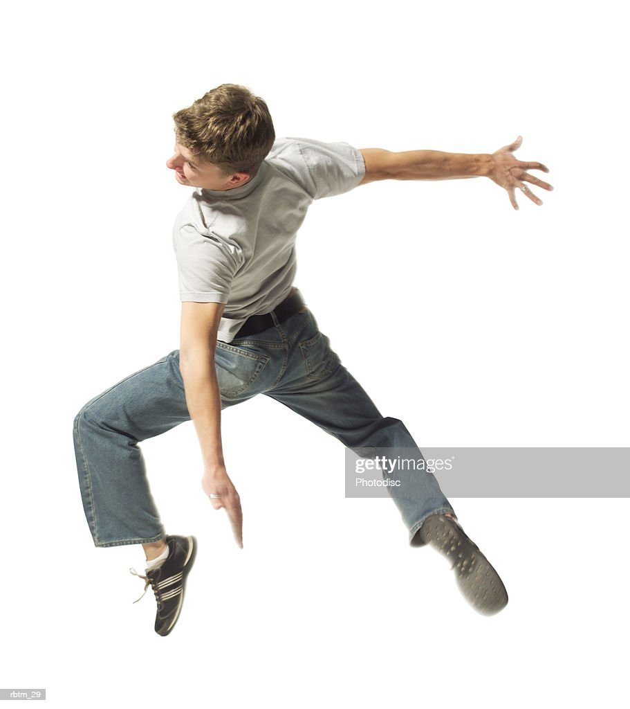 a caucasian male teen in jeans and a grey shirt jumps and spins through the air : Foto de stock