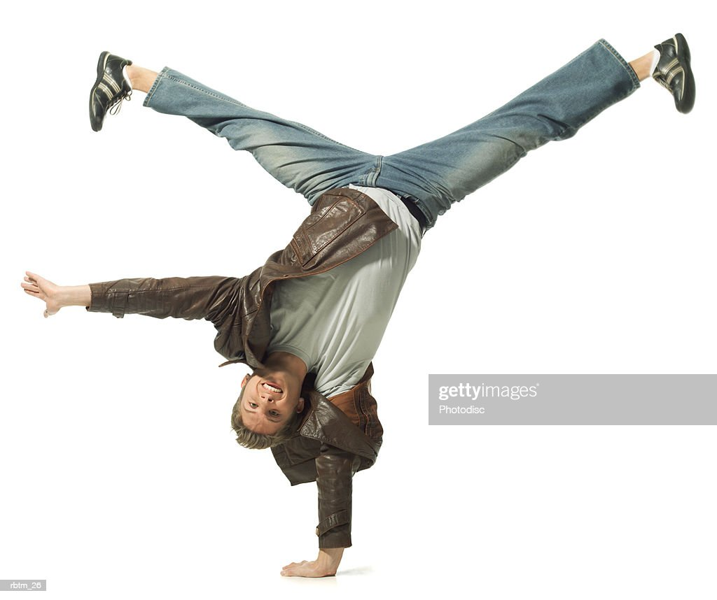 a caucasian male teen in jeans and a leather jacket does a cartwheel : Foto de stock