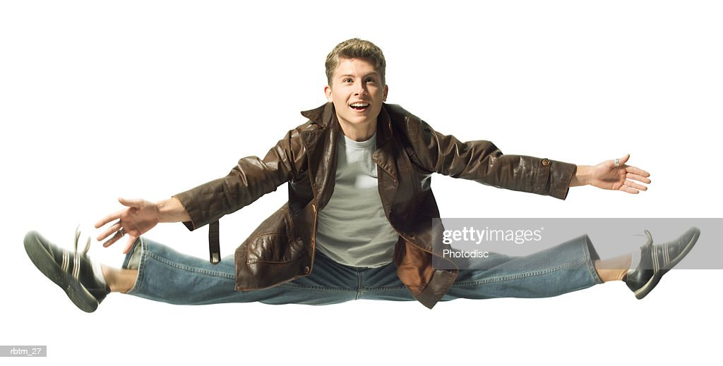 a caucasian male teen in jeans and a leather jacket jumps up and does the splits : Foto de stock