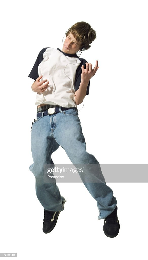 a caucasian male teen in jeans and a t shirt jumps up and plays air guitar while listening to music : Foto de stock