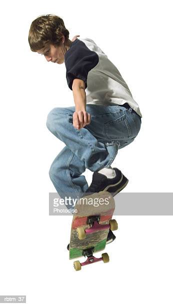 a caucasian male teen in jeans and a t shirt jumps up while riding his skateboard - ollie pictures stock pictures, royalty-free photos & images