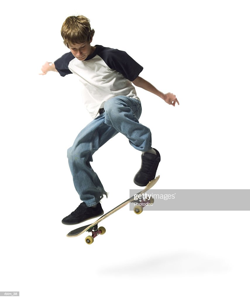 a caucasian male teen in jeans and a t shirt jumps up while riding his skateboard : Foto de stock