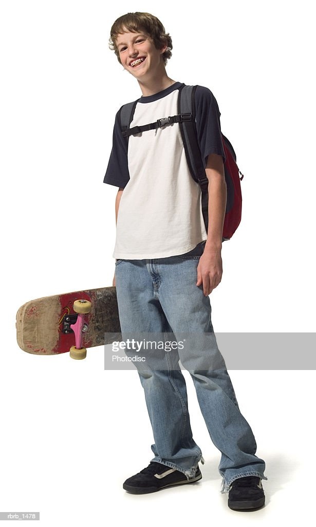 a caucasian male teen in jeans and a white and blue shirt stands with his backpack and skateboard : Stock Photo