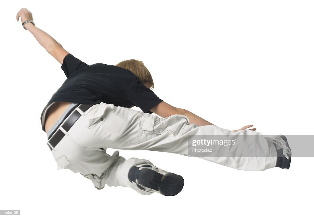 a caucasian male teen in tan pants and a black shirt jumps and kicks through the air : Foto de stock