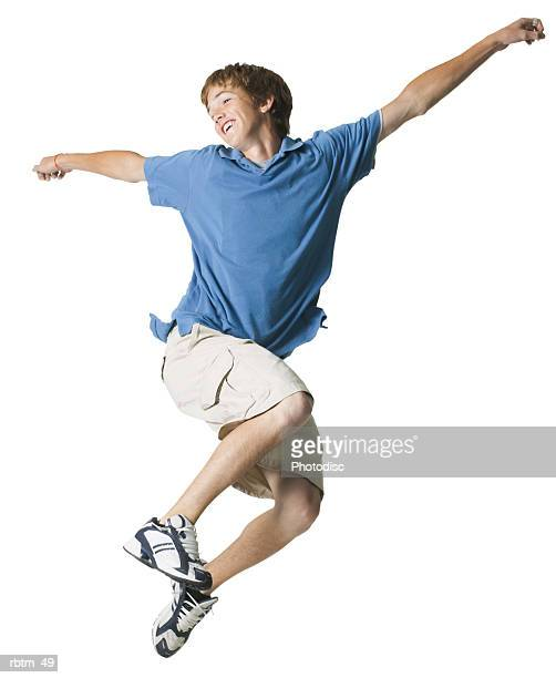 a caucasian male teen in tan shorts and a blue shirt jumps through the air