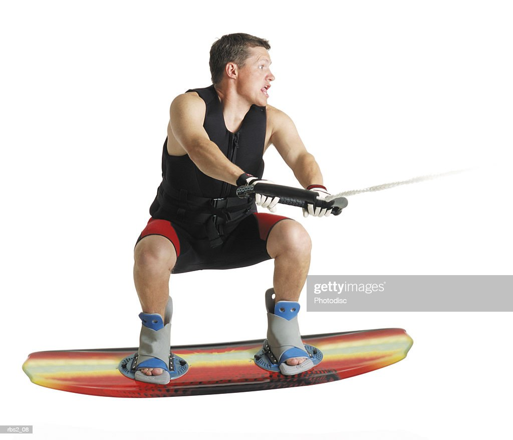 a caucasian male wakeboarder in a black lifejacket stands gripping the tow line and jumping in the air on his board : Stockfoto