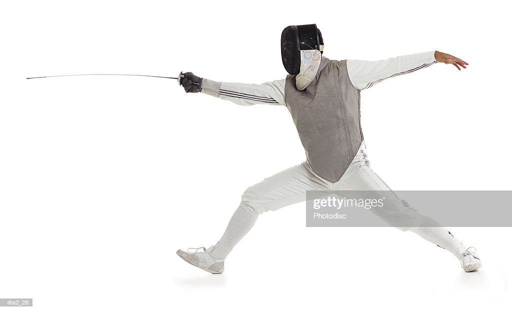 a caucasian male wearing a mask and protective gear lunges forward with his sword while fencing : Foto de stock