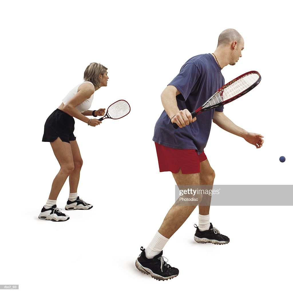 a caucasian man and woman are facing towards the side as they hold rakets and play raketball : Foto de stock