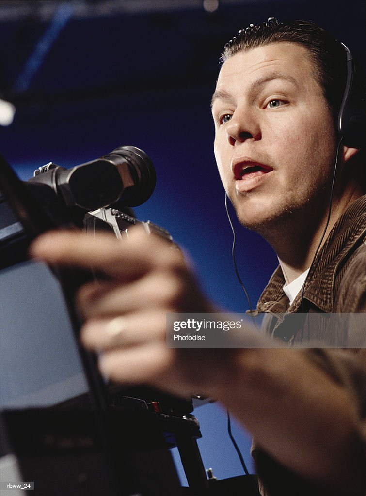 a caucasian man directs from behind the camera : Stockfoto