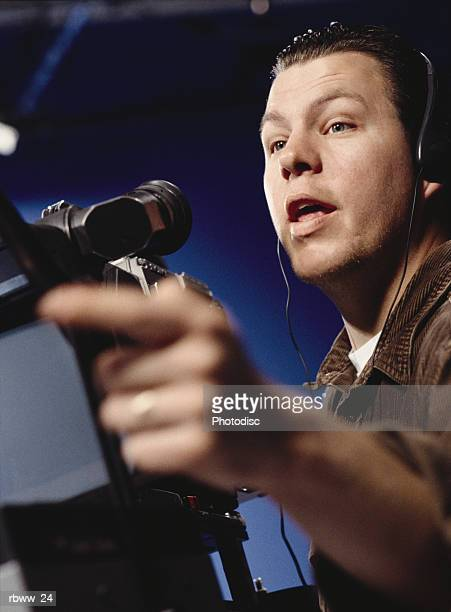 a caucasian man directs from behind the camera