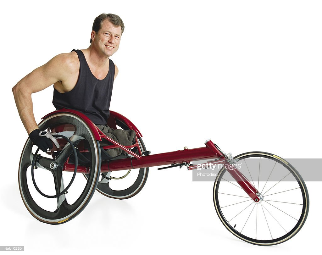 a caucasian man in a red racing wheel chair with his hands on the wheels wears a black tank top and smiles : Stockfoto