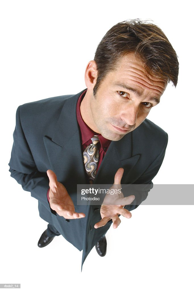 a caucasian man in a suit gestures with his hands and smirks up at the camera : Foto de stock