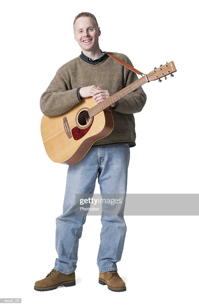 a caucasian man in jeans and a green sweater stand holds his guitar and smiles : Foto de stock
