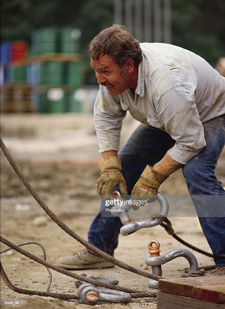 a caucasian man ties down some cables : Foto de stock