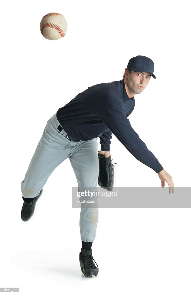a caucasian man wearing a blue and white baseball uniform is leaning forward after throwing a ball : Foto de stock