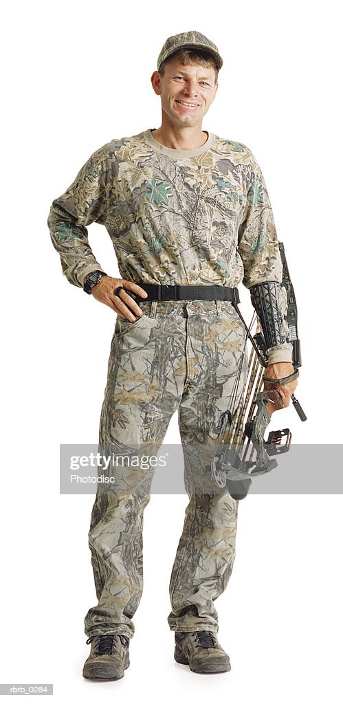 a caucasian man wearing army fatigues is standing and holding his archery equipment with his hand on his hip : Stockfoto