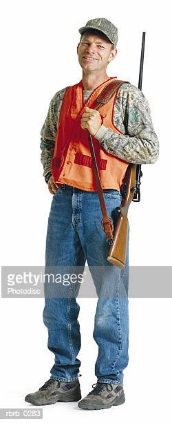 a caucasian man wearing jeans and an orange vest has on a hat as he slings his rifle strap over his shoulder