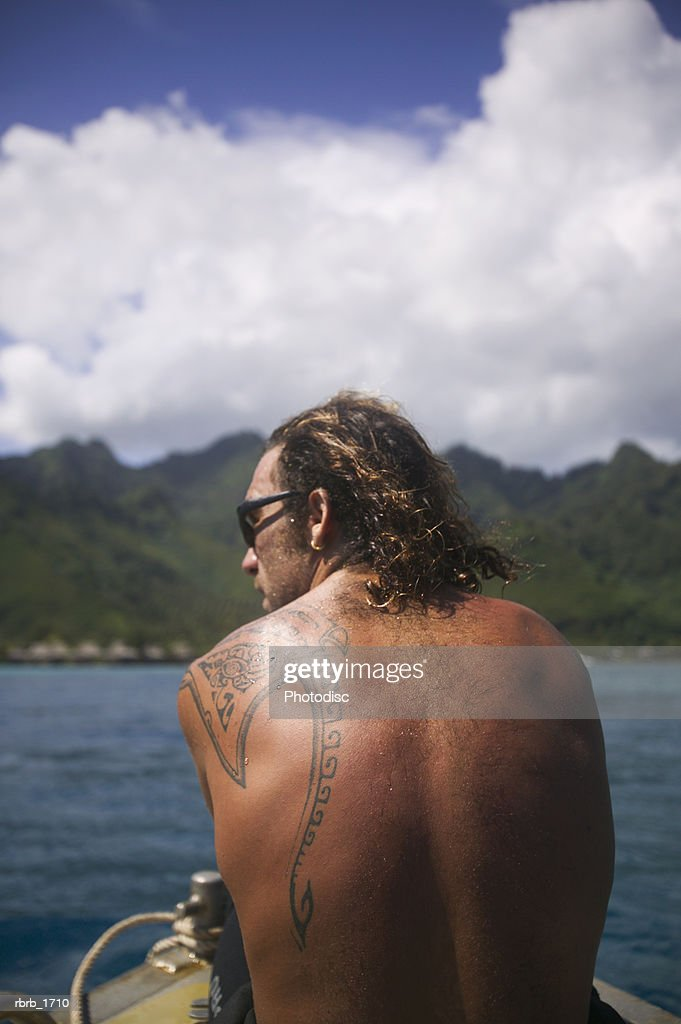 a caucasian man with a tattoo rides on a boat while vacationing in the tropics : Stockfoto