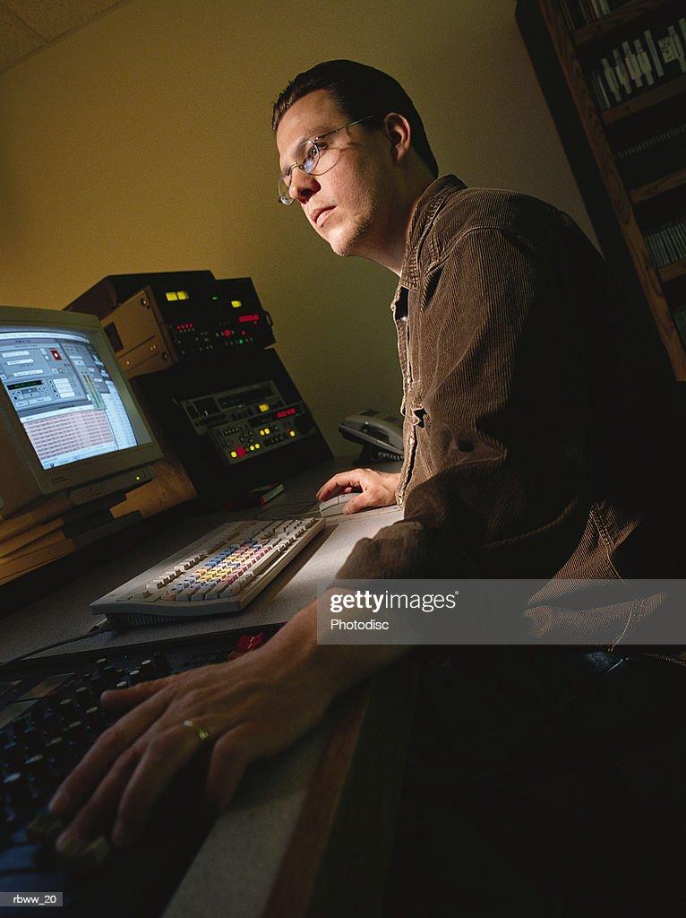 a caucasian man works as a video editor : Foto de stock