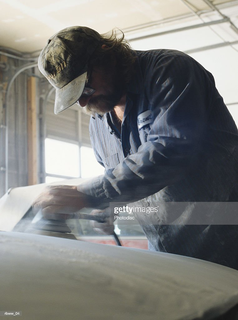 a caucasian man works on a car in a shop : Stockfoto