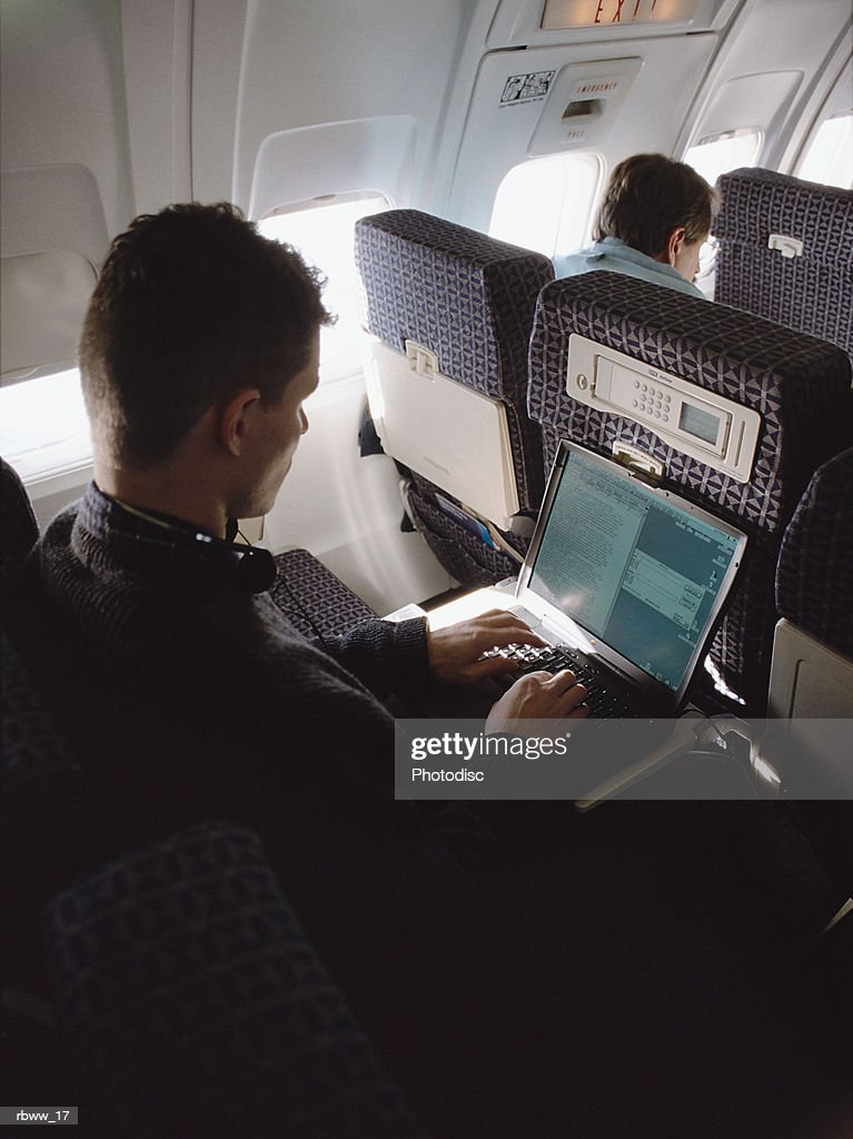 a caucasian man works on his laptop computer on an airplane : Foto de stock