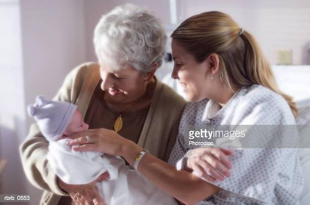 a caucasian mother introduces her newborn baby to her grandmother in a hospital recovery room