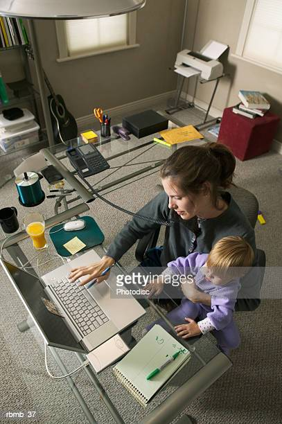 a caucasian mother sits working in her home office on the phone with her young daughter on her lap