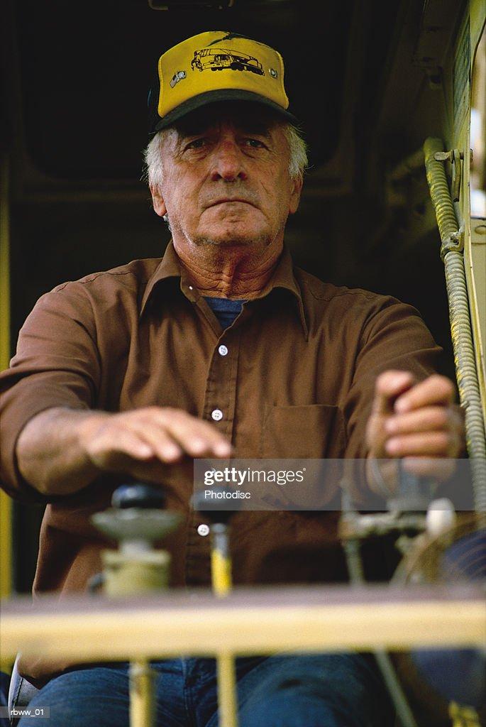 a caucasian older man operates construction machinery : Foto de stock