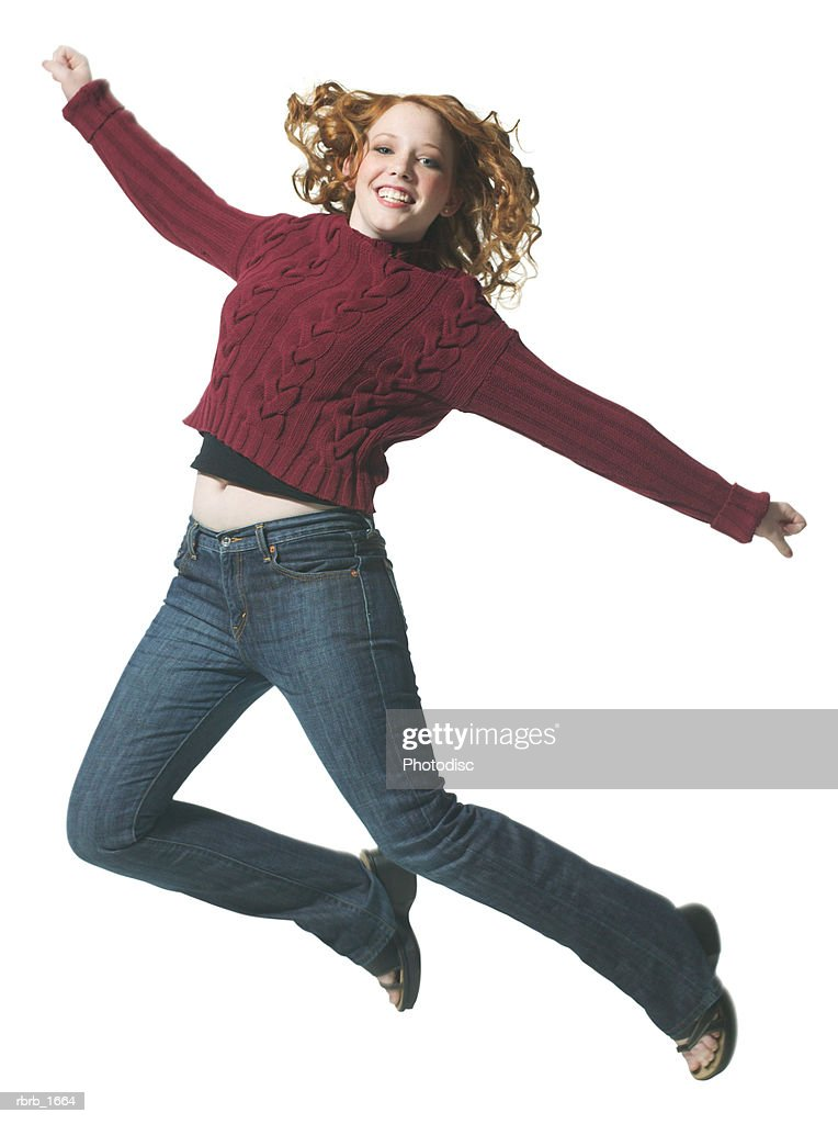 a caucasian redheaded female teen in jeans and a red sweater jumps playfully through the air : Stockfoto