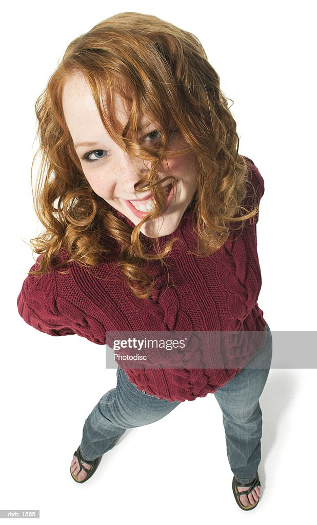 a caucasian redheaded female teen in jeans and a red sweater smiles up at the camera : Stockfoto