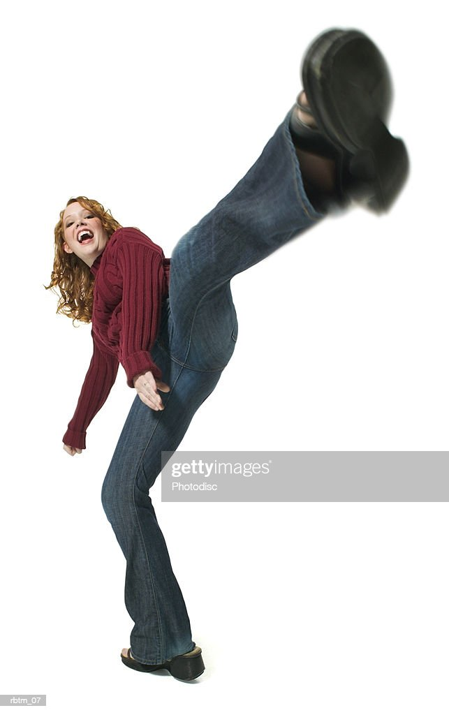 a caucasian redheaded teenage girl in a red sweater and jeans kicks up playfully into the air : Foto de stock