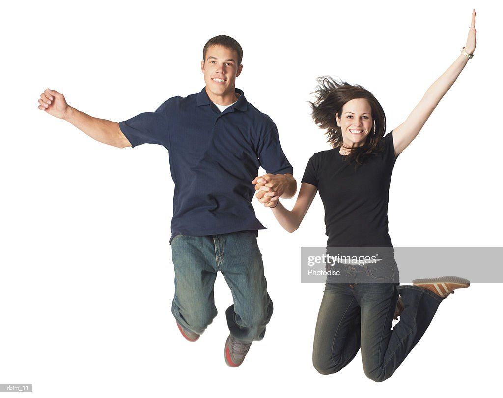 a caucasian teen couple hold hands as they jump up playfully and smile : Foto de stock