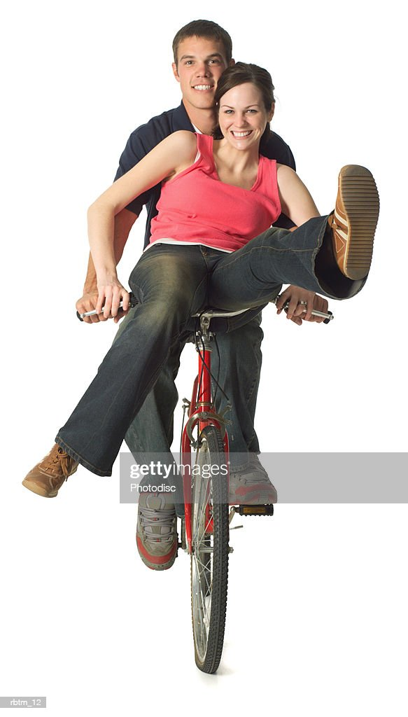 a caucasian teen couple ride and play together on a bicycle : Foto de stock