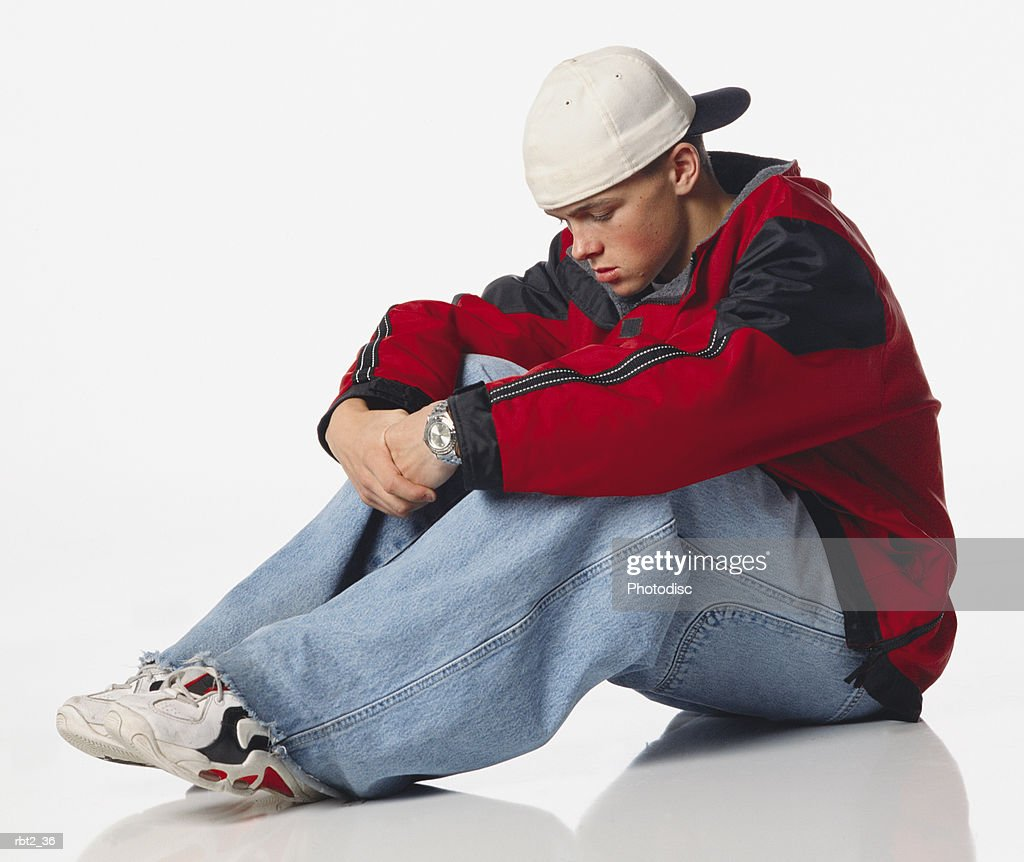 a caucasian teenage boy in a red coat and baggy jeans and backwards baseball cap sits crosswise on the floor looking sad : Foto de stock