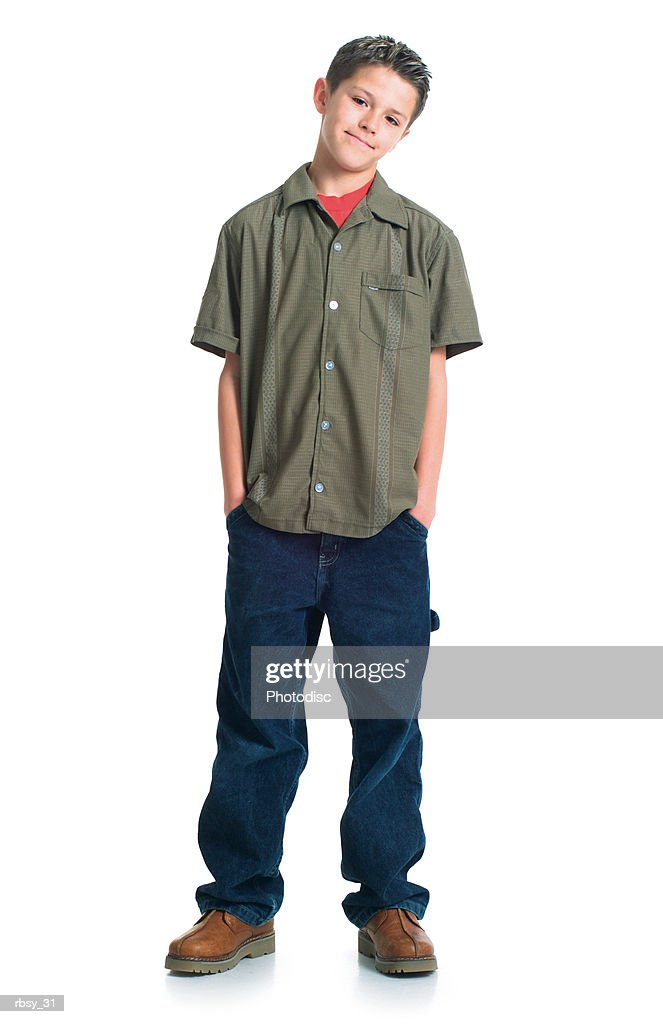 a caucasian teenage boy in jeans and a green shirt tosses his head to the side and smiles : Stockfoto