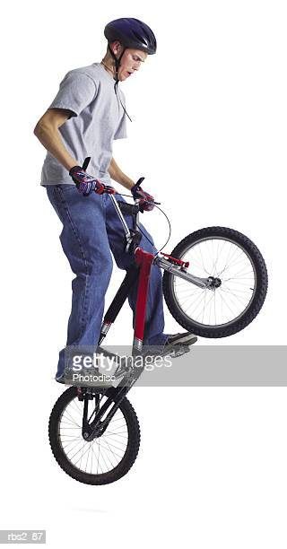 a caucasian teenage boy is wearing a bike helmet as her performs a stunt on his red bike with its front wheel is in the air