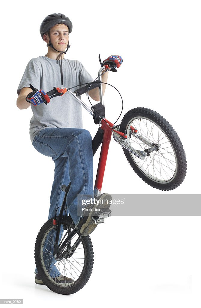 a caucasian teenage boy wearing jeans and a bike helmet is posing with his dirt bike as he lifts the front wheel in the air : Stockfoto