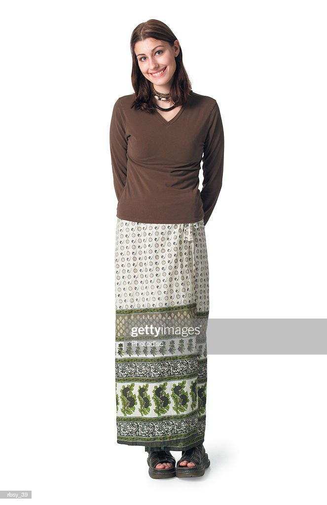 a caucasian teenage girl in a skirt and brown blouse puts her arms behind her back and smiles : Foto de stock