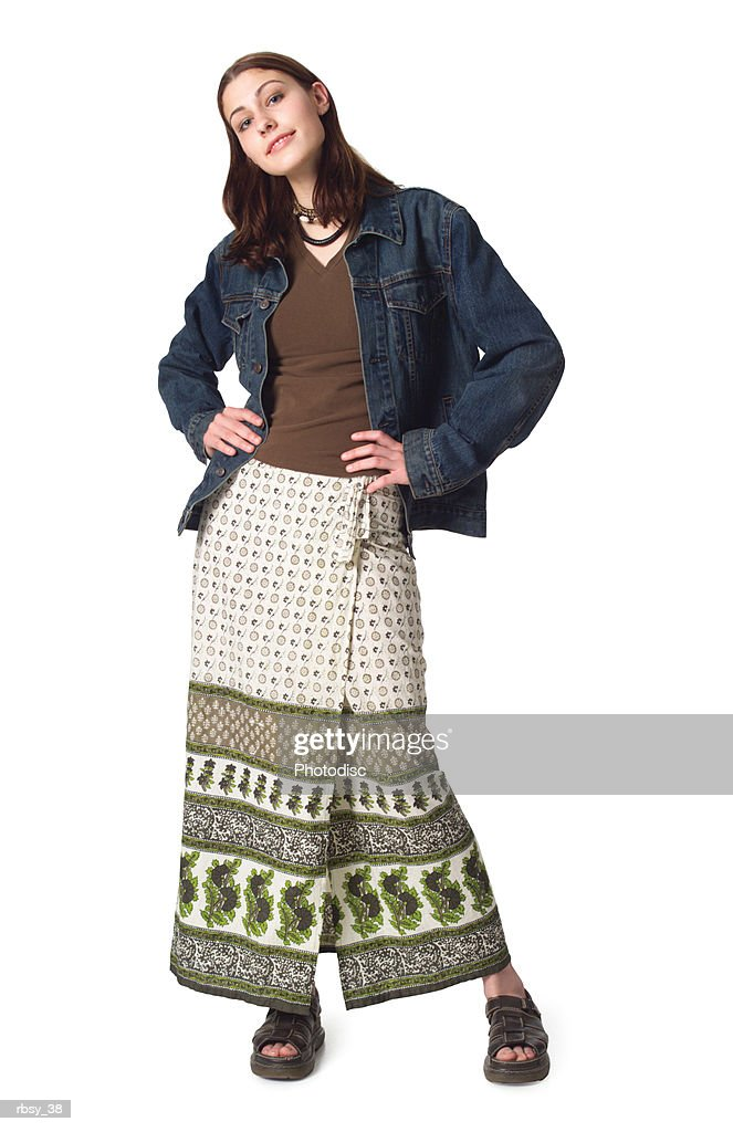 a caucasian teenage girl in a skirt and jean jacket puts her hands on her hips and smiles : Foto de stock