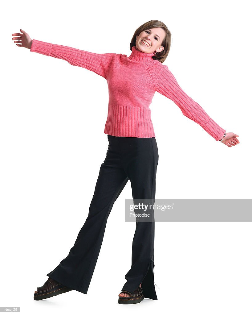 a caucasian teenage girl in black pants and a pink sweater stretches out her arms and smiles : Foto de stock