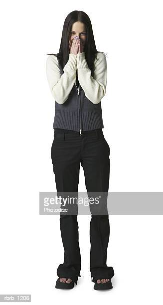 a caucasian teenage girl in black pants and a white and grey sweater holds her hands to her face in embarrassment - funny black girl ストックフォトと画像