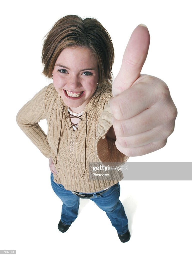 a caucasian teenage girl in jeans and a tan sweater gives the thumbs up sign up into the camera : Foto de stock