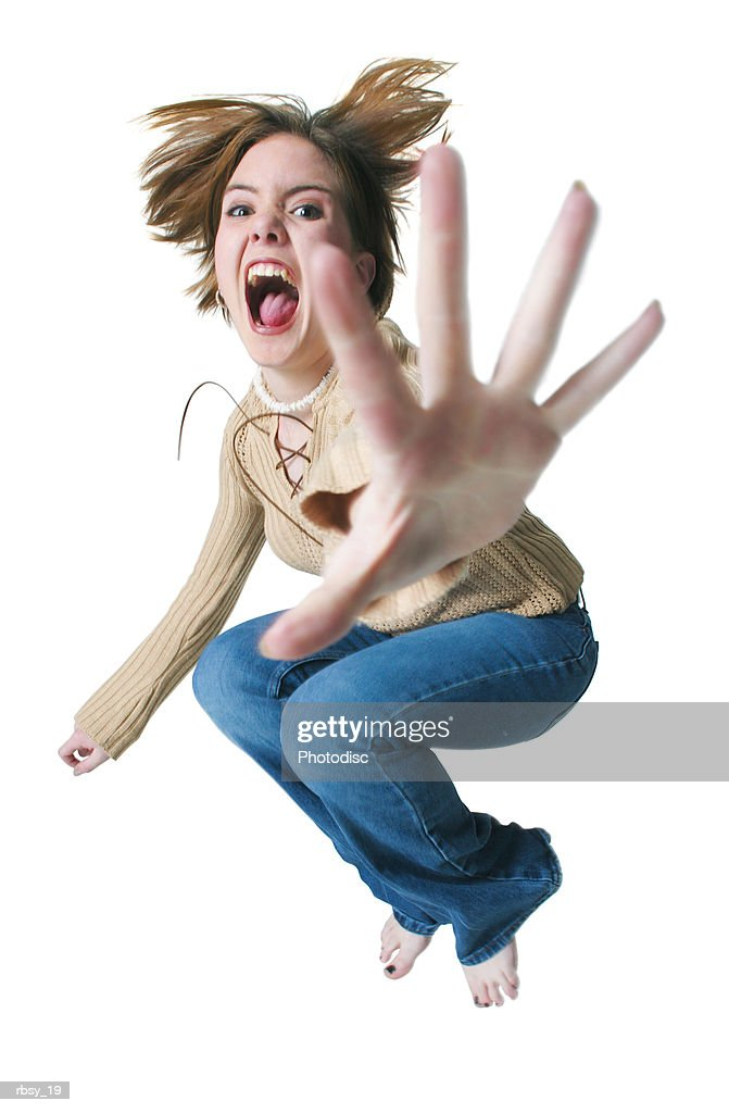a caucasian teenage girl in jeans and a tan sweater jumps into the air and throws her hand forward : Foto de stock