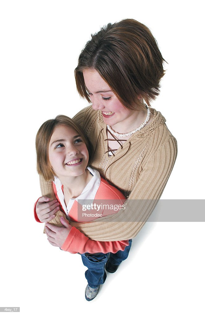 a caucasian teenage girl in jeans and a tan sweater looks down as she hugs her little sister : Foto de stock